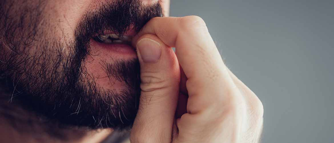 close-up of a bearded man chewing on his finger nails