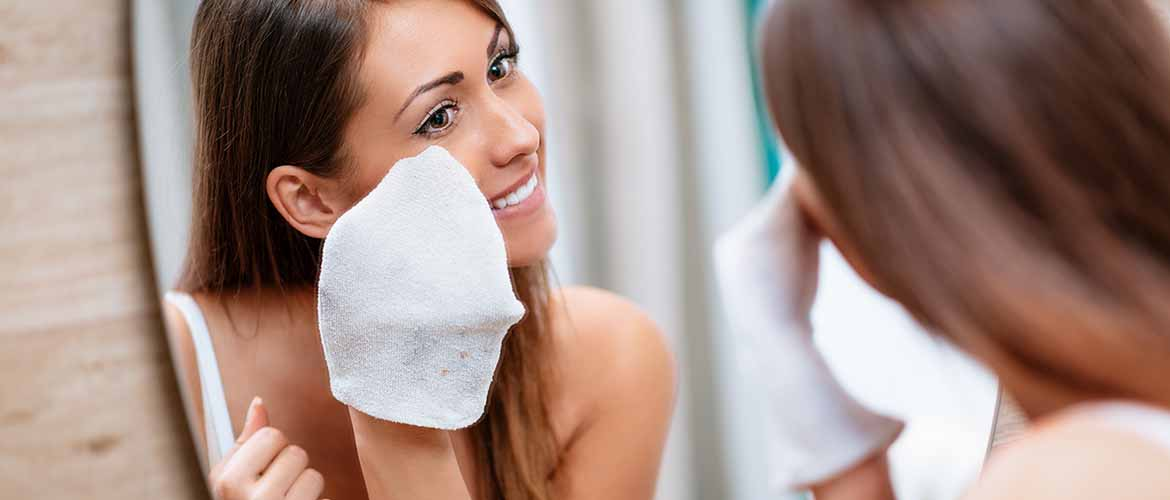 a woman removing makeup from her face with a washcloth