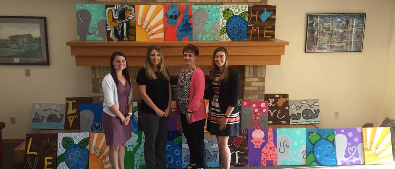 Four women standing in a room full of artwork