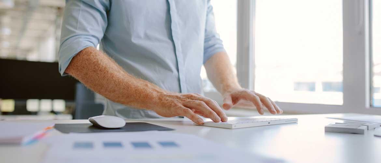 man typing at standing desk