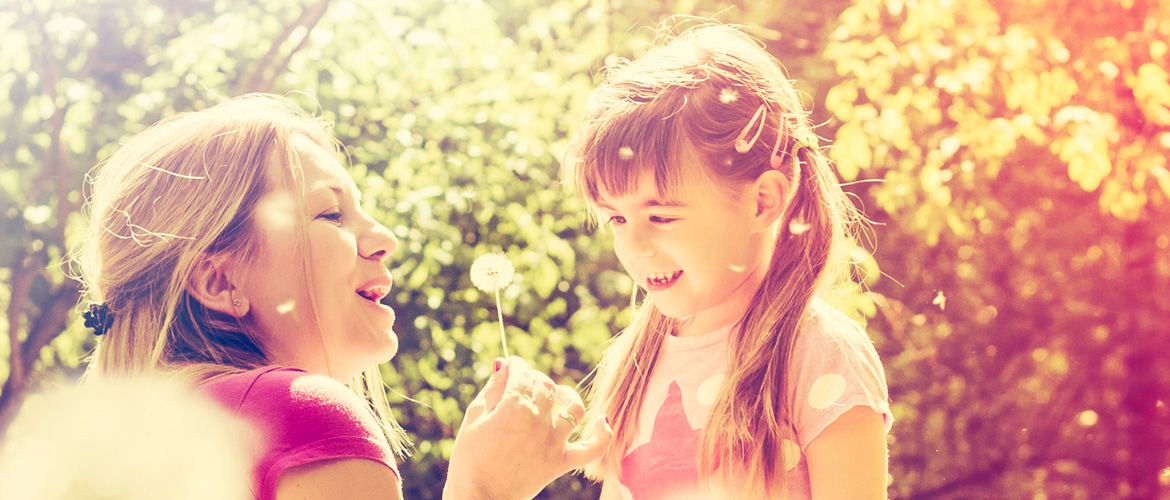 Mother and daughter blowing dandelions in the garden