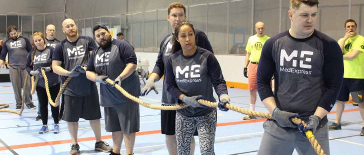 Arlene Neal and several other MedExpress employees participate in tug-of-war during a charity event