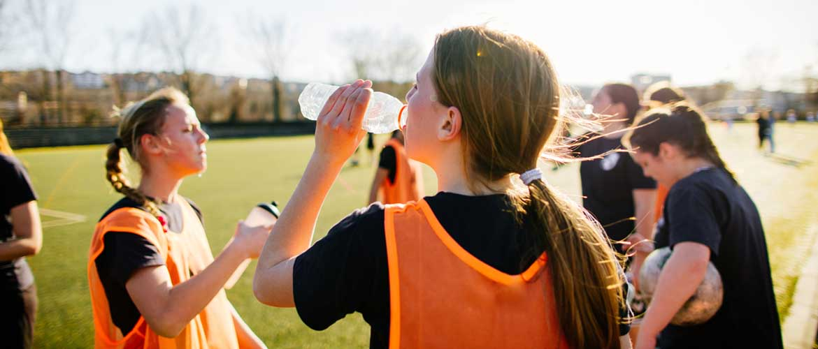 young women athletes drinking water during a match