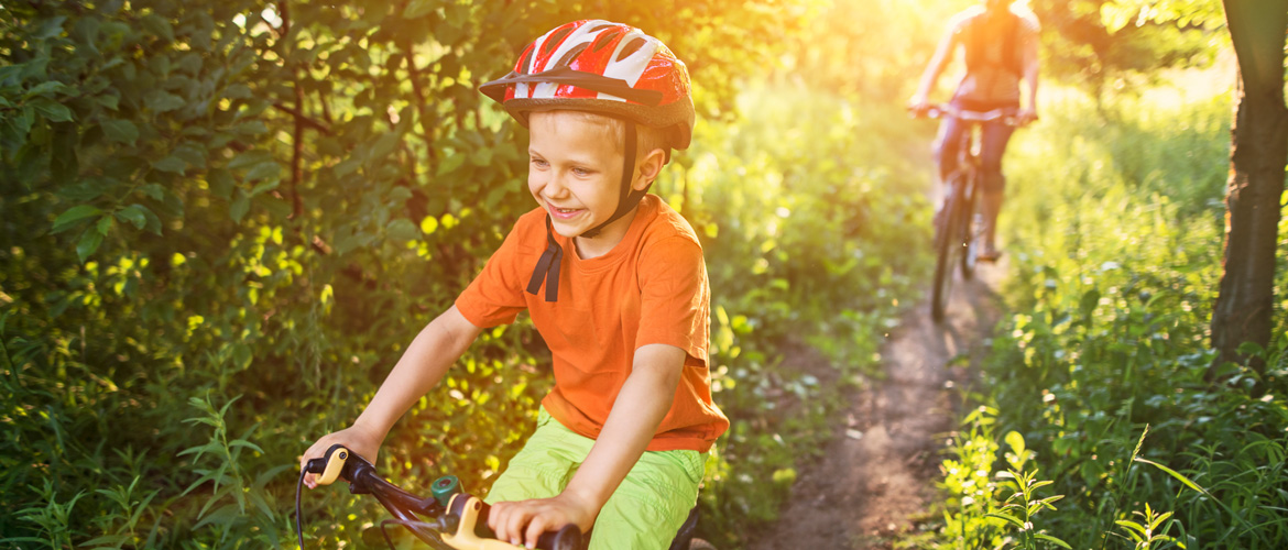 Young boy wearing a helmet riding his bike through a woodsy area and another person on a bike a few feet behind him.