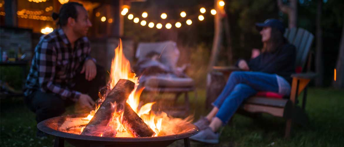 a man and woman sitting outside next to a campfire