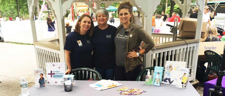 Three MedExpress employees at a table at Idlewild Park in Ligonier, Pennsylvania