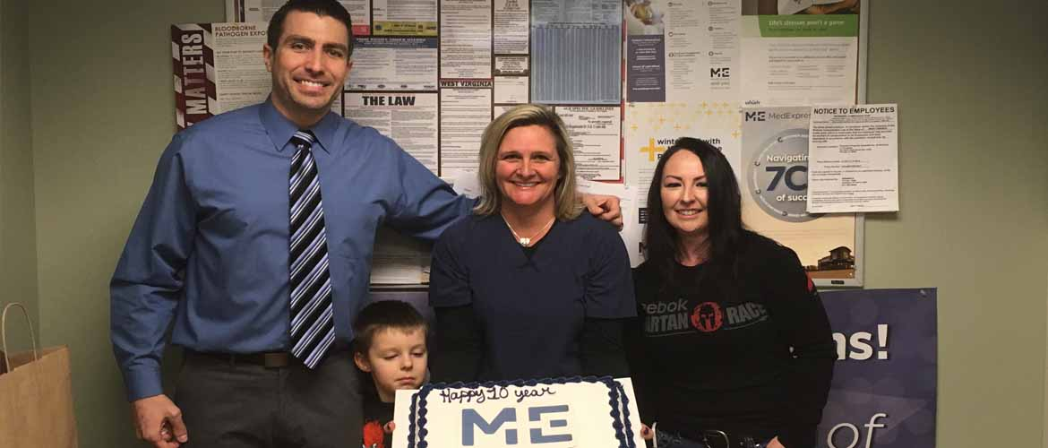 Tracie Dilliner holds a cake celebrating her 10th work anniversary with MedExpress while surrounded by some of her co-workers