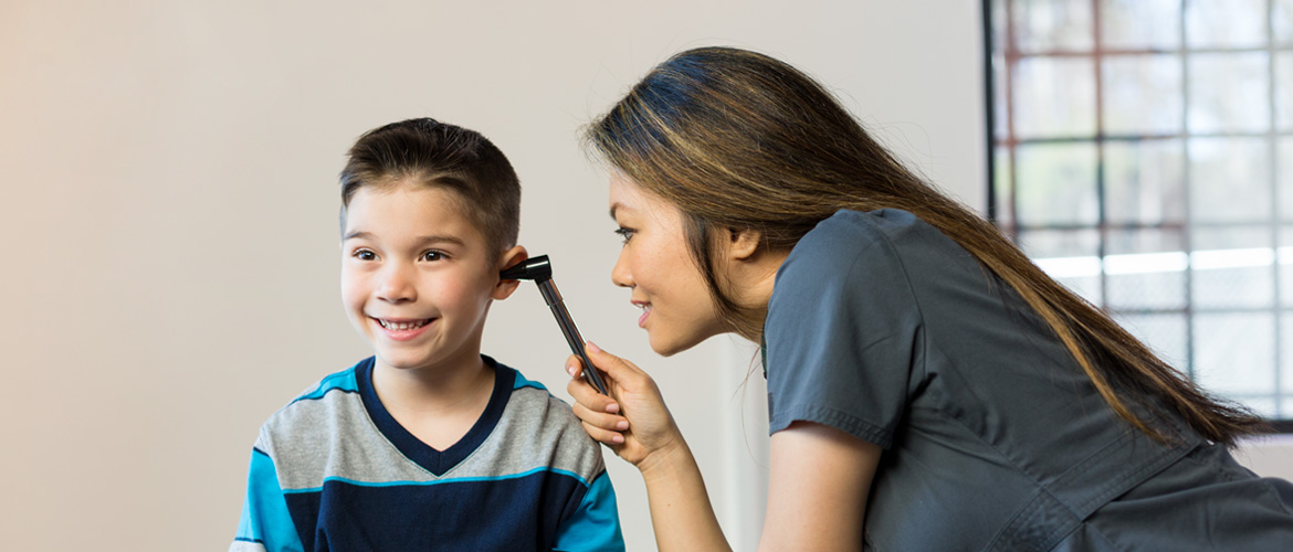 Doctor checking young boy's ear