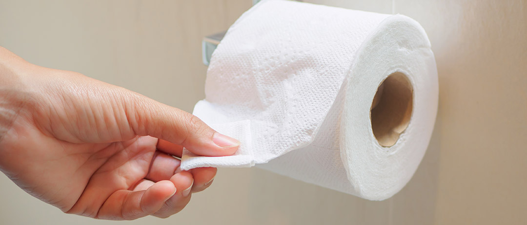 a person pulling a sheet off a toilet paper roll in a bathroom