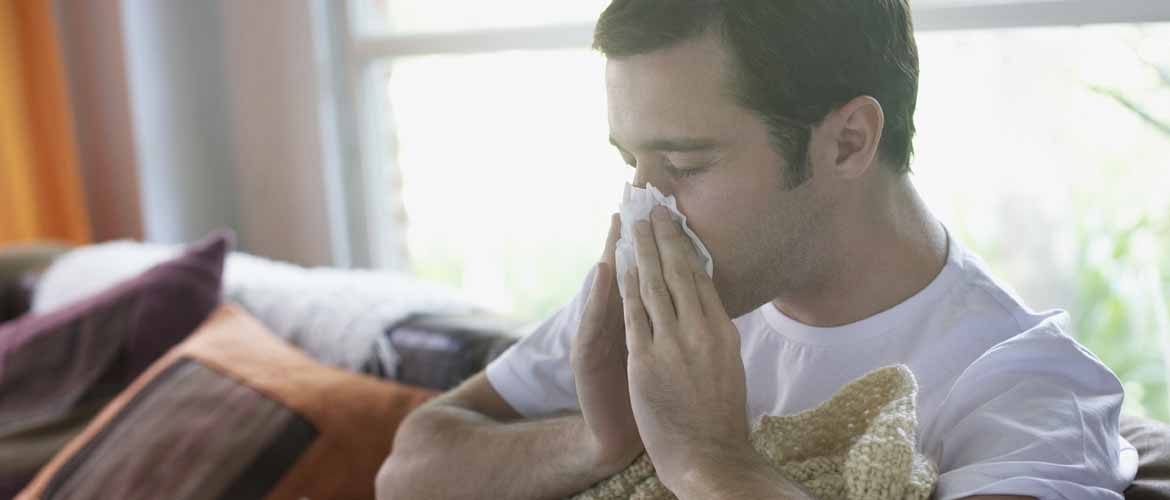 a man sitting on a couch blowing his nose into a tissue