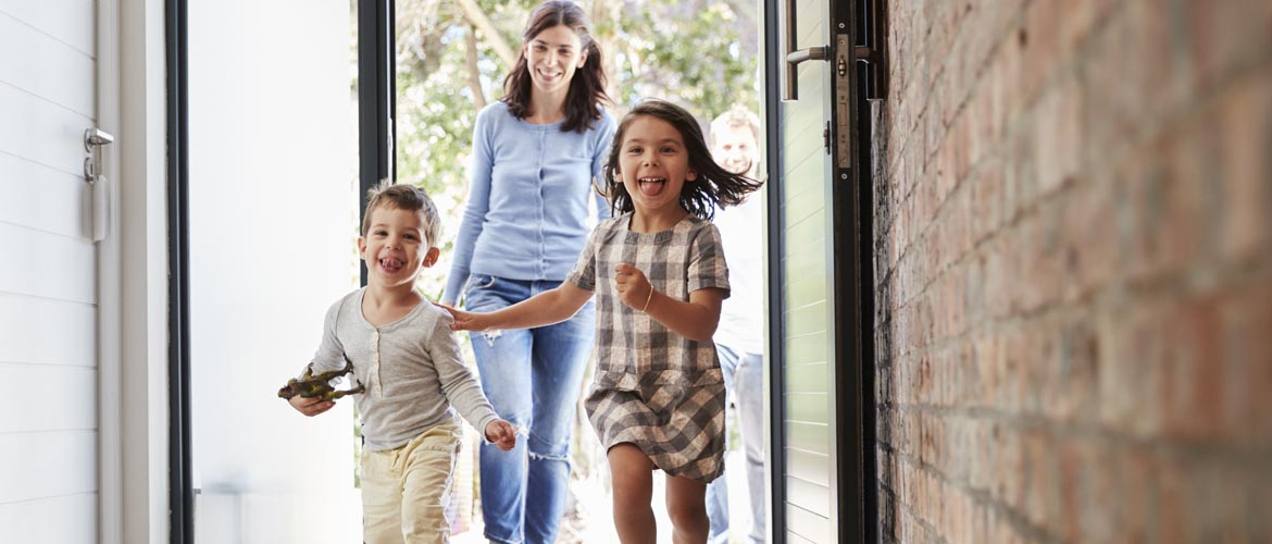 mother and two children entering their house
