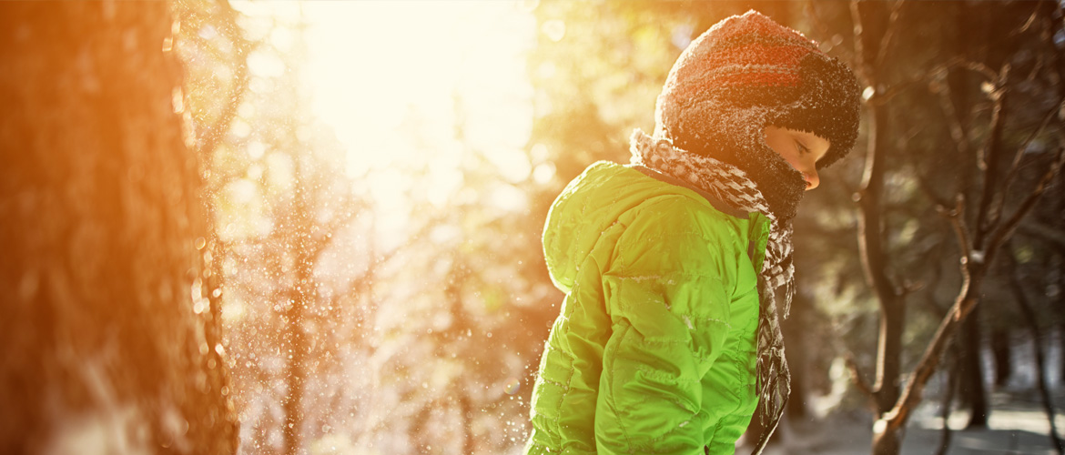 A young child outdoors in the snow wearing a heavy lime green jacket and fleece beanie face mask