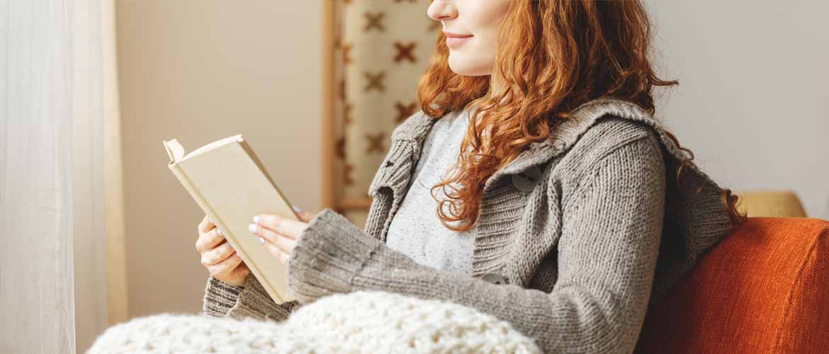 woman sitting on a couch reading a book