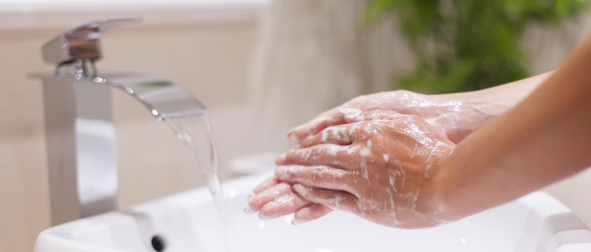 Hands covered in soapy lather at a sink with water running from the faucet