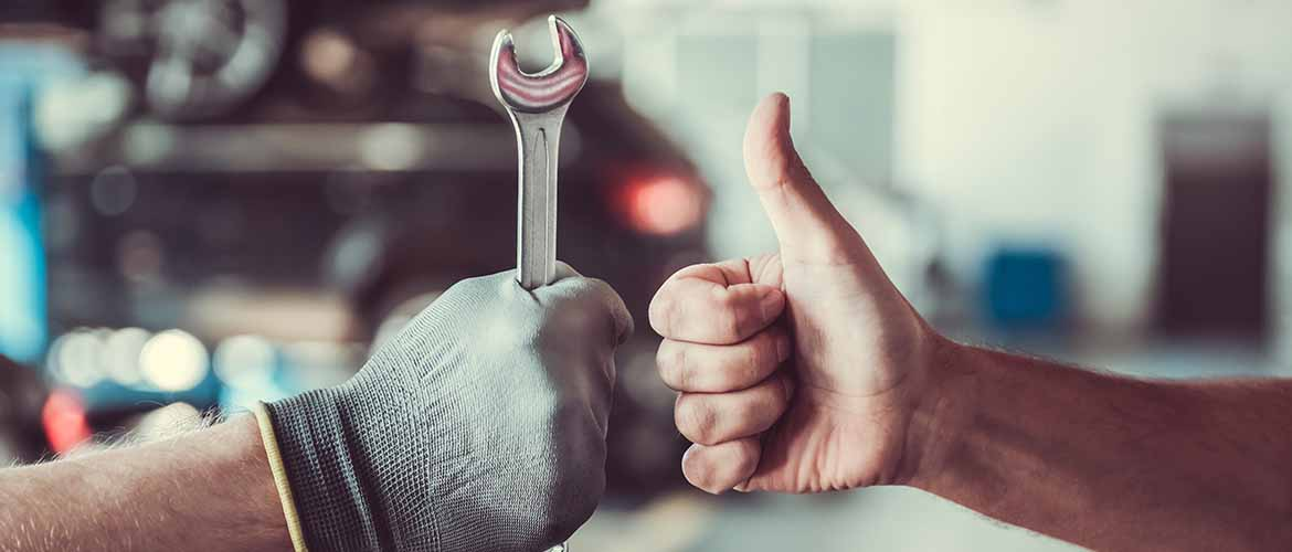 two mechanics working in auto service. One is holding a spanner, while the other is giving a thumbs up