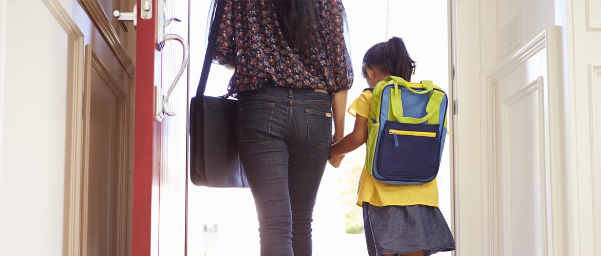 Rear view of a small school girl wearing a backpack holding her mom's hand and walking out the door