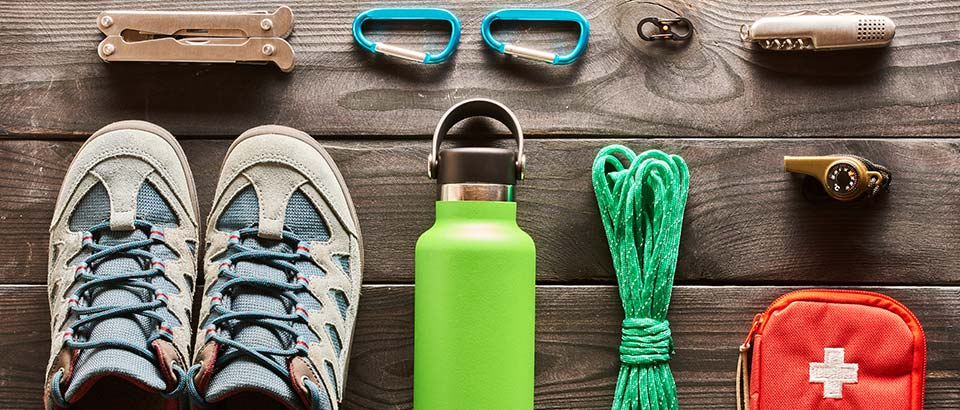 hiking gear, including a water bottle, sneaker, and first-aid kit, laid out on a wood table