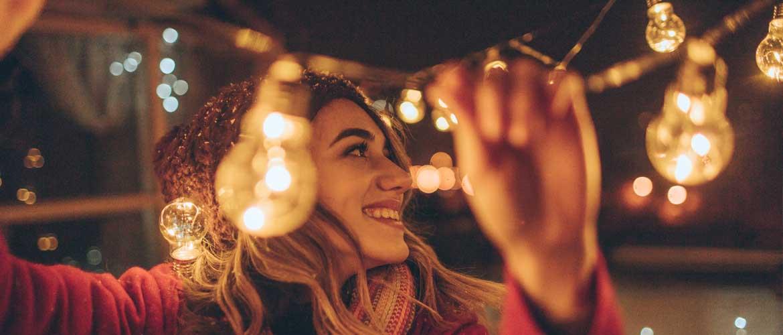 smiling woman hanging lights