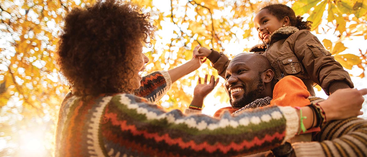 Father, mother and child outdoors among the fall leaves playing and laughing