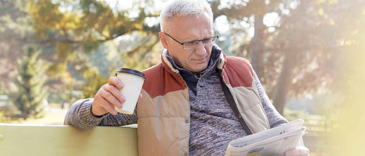 man drinking coffee and reading the paper
