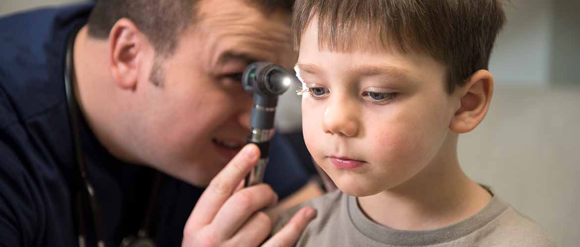 a MedExpress medical professional examining a young boy's ear