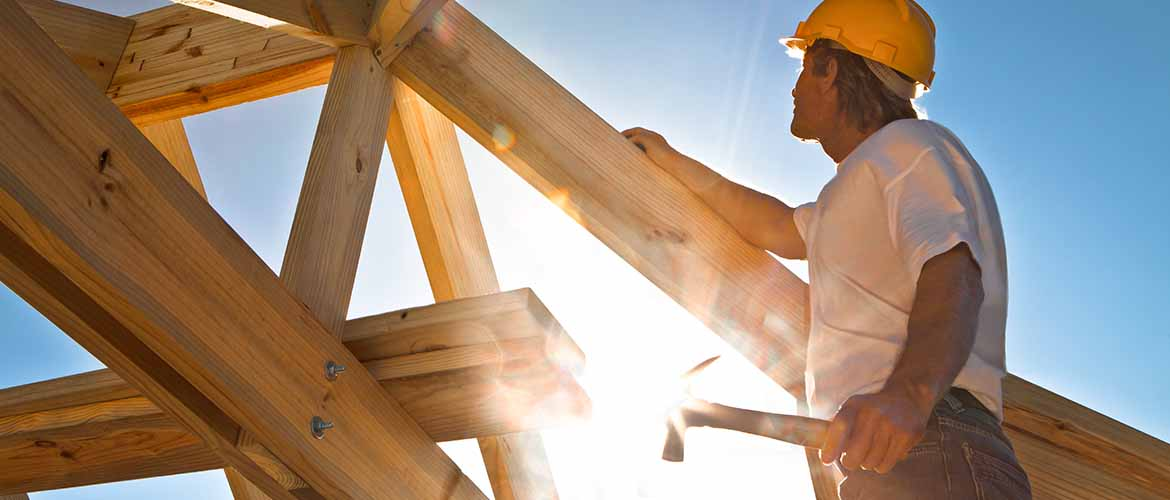 a construction worker standing outside in the frame of a house with a hammer in his hand