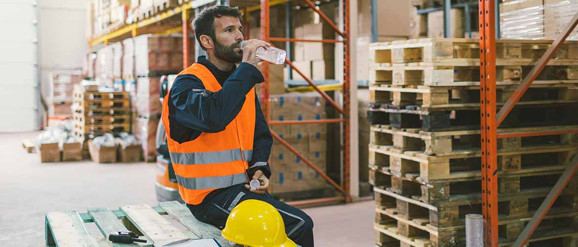 a warehouse worker sitting on a wooden crate drinking a bottle of water