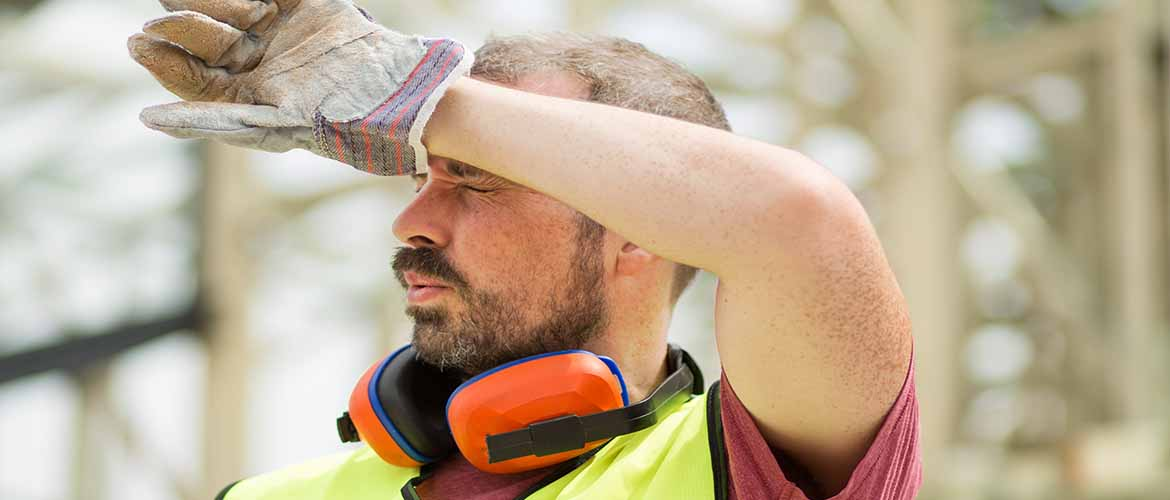 a construction worker wiping sweat from his forehead