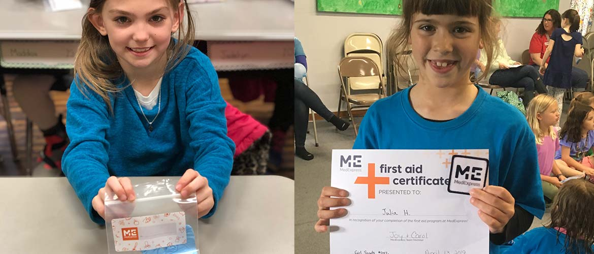 one young girl holding up a first-aid kit and another young girl holding up her first-aid kit completion certificate