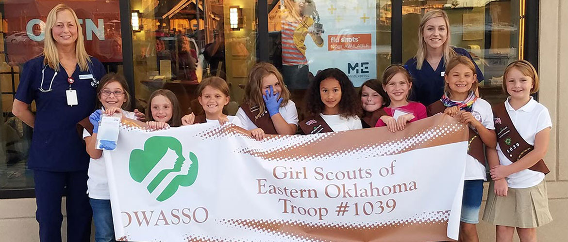 a Girl Scouts troop standing outside a MedExpress building with two MedExpress team members
