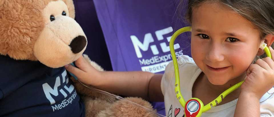 little girl holding a stethoscope to Sniffles the teddy bear's chest