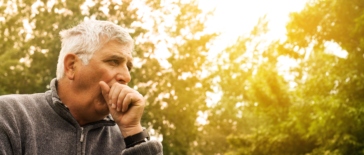 Senior man outdoors near trees coughing