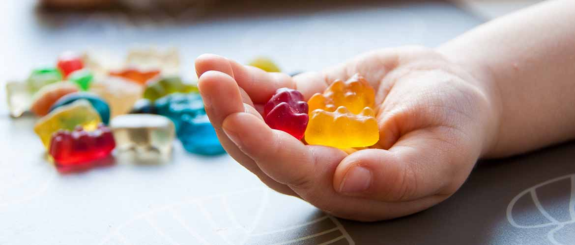 a hand holding several gummy bears with more gummy bears nearby