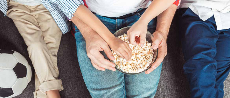 three people enjoying a bowl of popcorn together