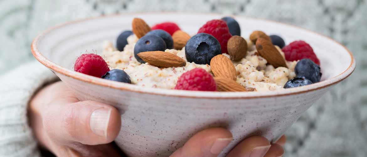 a person holding a bowl of oatmeal with berries and nuts on top