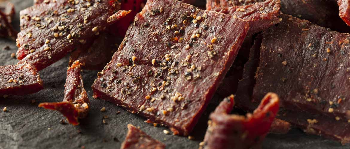 a pile of dried, peppered beef jerky cut in strips for a grab and go snack