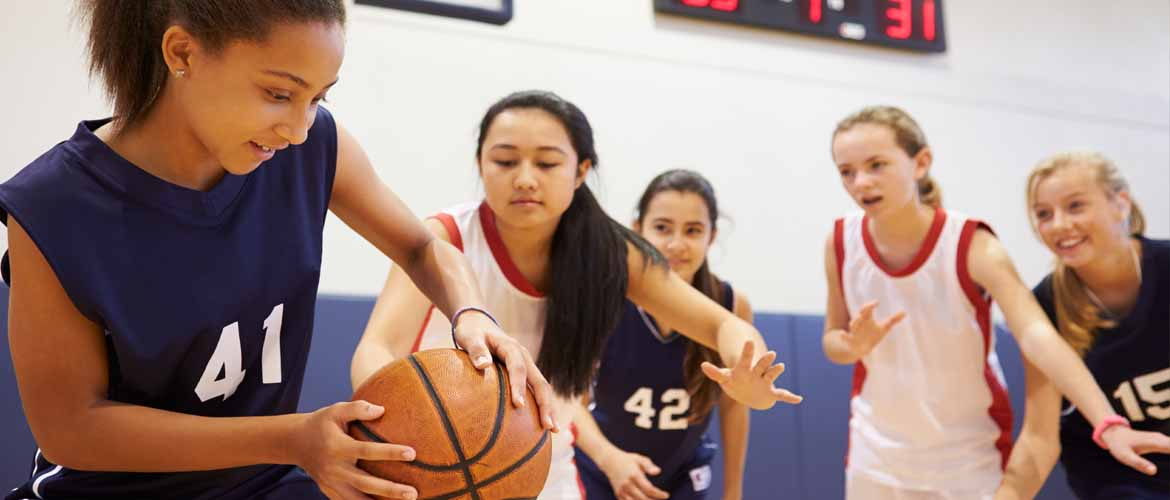 group of girls playing a basketball game