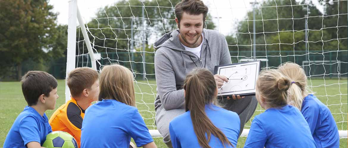 young soccer players sitting before their coach as he explains a play drawn on a whiteboard