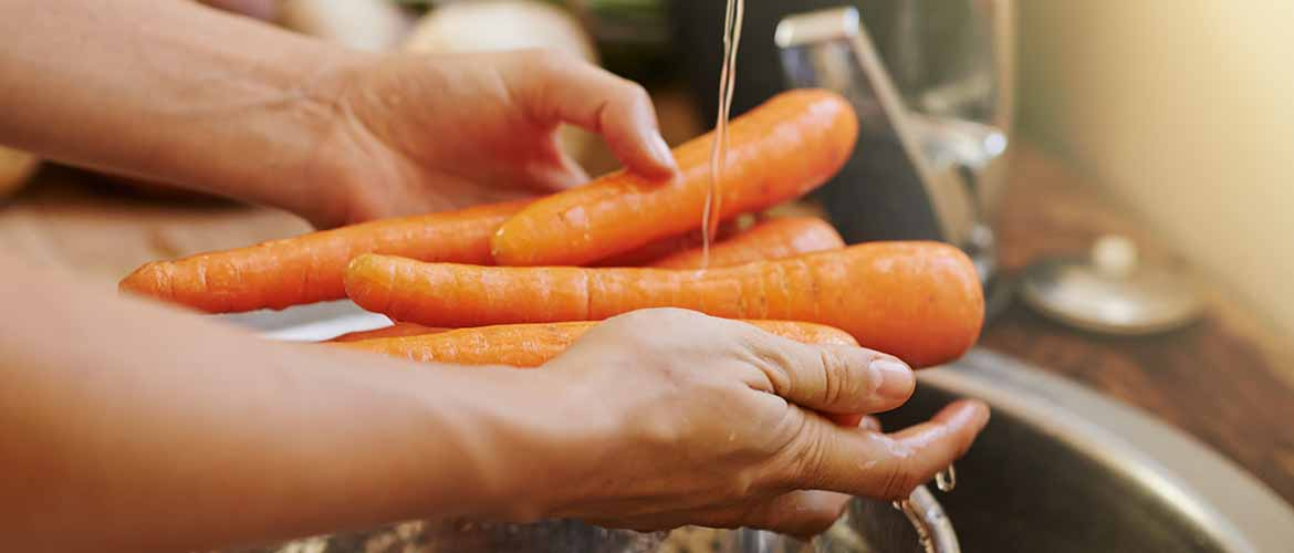 a person washing carrots over a sink