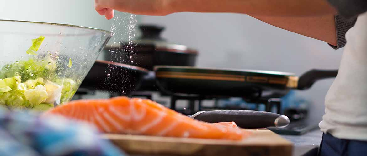 a person salting a piece of salmon