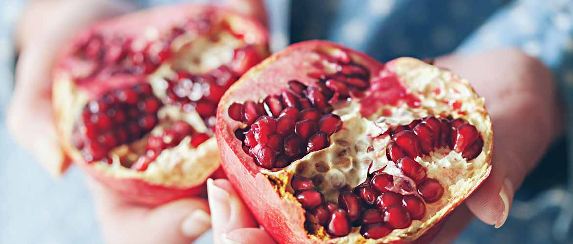 a person holding a pomegranate that's cut in half