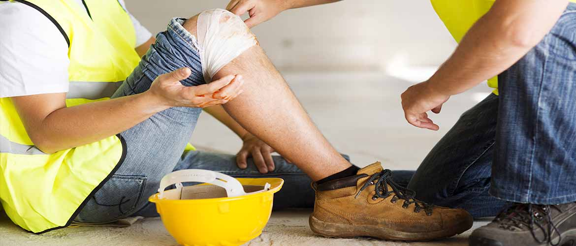 a coworker tends to a construction worker who has an injured knee