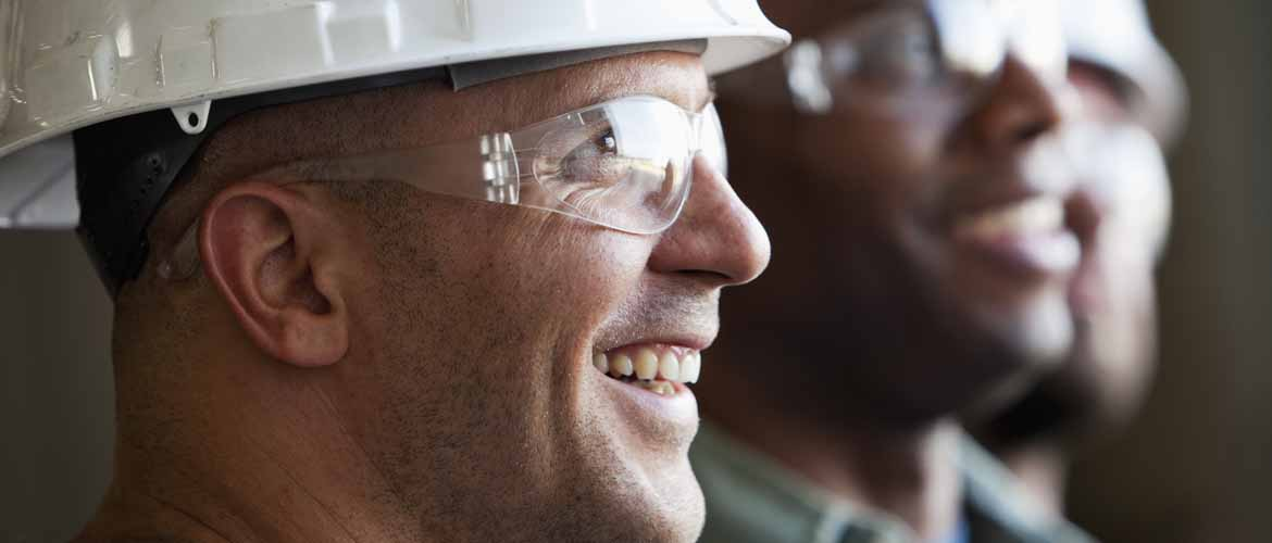 Close up of group of construction workers wearing hard hats and safety glasses