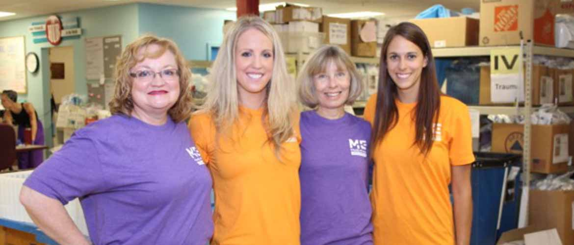 four MedExpress employees standing together in their volunteer T-shirts
