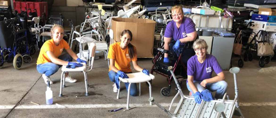 four MedExpress volunteers cleaning medical materials during their day at Global Links