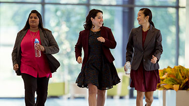 Image of three female professionals walking through the office