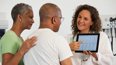 Image of a doctor showing information to her patient and his wife on a tablet
