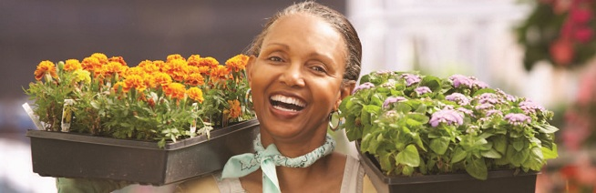 Smiling women carrying new flowers to plant
