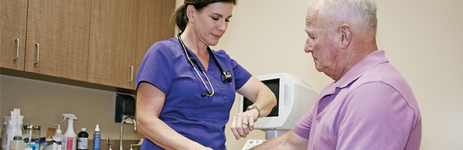 health care professional taking senior patient's pulse