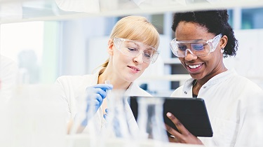 Female scientists looking at a tablet